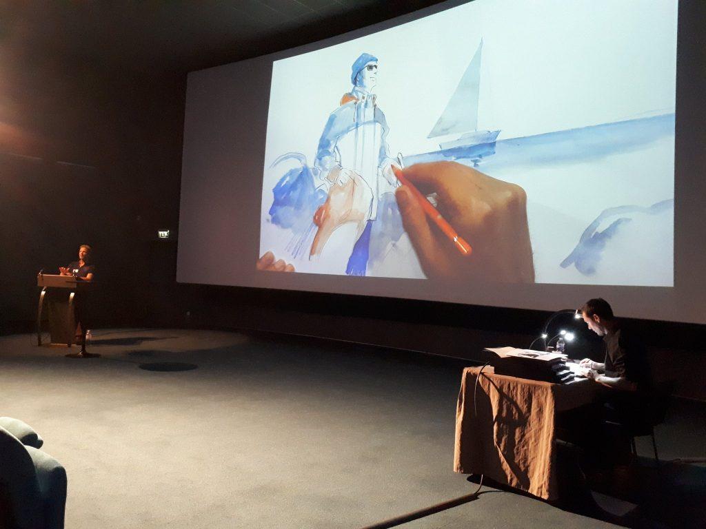 Mathieu Simonnet conte et Laurent Richard illustre dans l'auditorium. Sur le dessin projeté à l'écran, un marin avec des lunettes et une canne blanche se trouve sur la plage, entre les rochers avec un volier en arrière plan.  en
