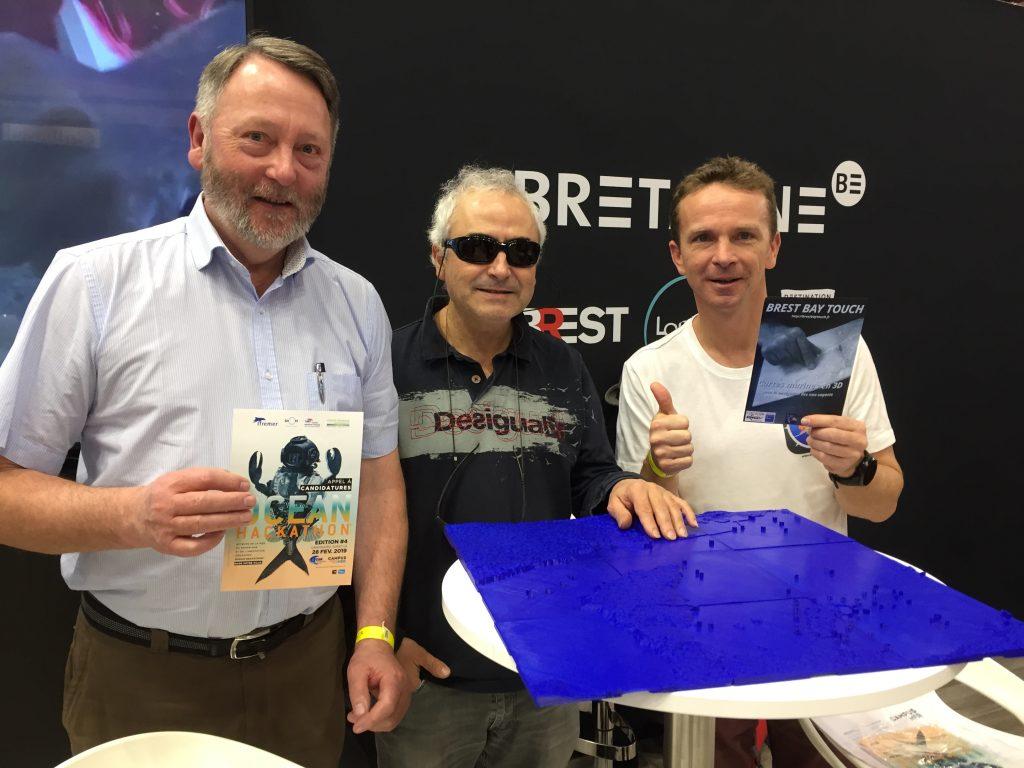 De gauche à droite, Serge Morvan tient un flyer de l'ocean hackathon, Olivier Ducruix touche la carte en relief et Mathieu Simonnet présente un flyer de Brest Bay Touch pour la fondation AFNIC. Tout le monde sourit et la rade en 9 tuiles bleues est bien une vue sur une table ronde haute.